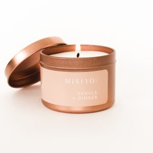 rose gold candle tin burning, scent is vanilla + ginger