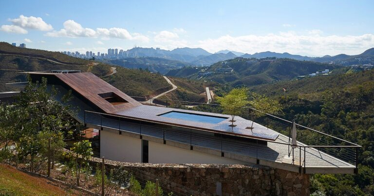 tetro tops residence with irregular deck roof opening towards mountainous views in brazil